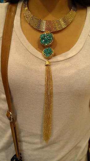 Gold plate necklace with blue minerals and gold tassel hanging down the center.